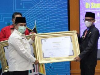 Pj. Bupati Heri Nofiardi saat menerima penghargaan TP2DD.