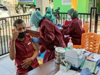 Seorang Lansia sedang di Vaksin.