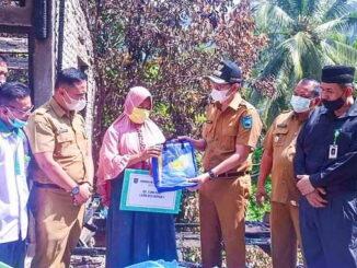 Walikota Sawahlunto menyerahkan bantuan disaksikan oleh Kepala Dinas Sosial dan Ketua BazNas Kota Sawahlunto.
