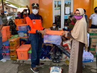 Bupati Limapuluh Kora menyerahkan bantuan untuk korban banjir di Manggilang.