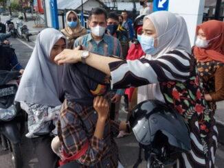 Ketua FKS Bukittinggi memasangkan masker kepada masarakat yang kedapatan tidak memakai masker.