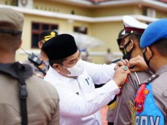 Pemasangan pita oleh Bupati Suhatri Bur kepada salah seorang anggota Polres Padang Pariaman sebagai pertanda dimulai operasi Ketupat Singgalang tahun 2021.