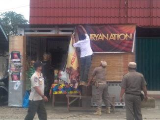 Petugas Satpol PP Payakunbuh tengah menurunkan spanduk iklan rokok yang terpajang di warung warga.