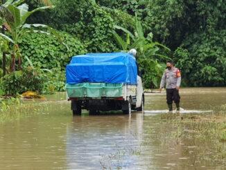 Petugas polisi saat memandu kenderaan di daerah yang kena banjir.