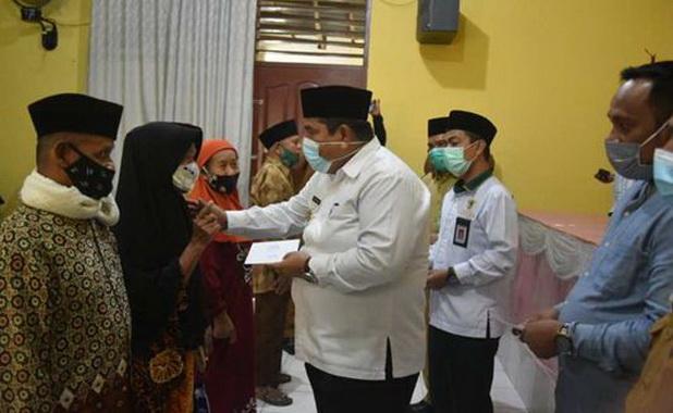 Bupati Suhatri Bur meynerahkan zakat fitrah kepada perwakilan mustahik yang berhak menerimanya di Kecamatan V Koto Timur.