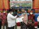 Bupati Padang Pariaman Suhatri Bur menyerahkan secara simbolis kepada Asni Sanan uang ganti kerugiaan pengadaan tanah untuk pembangunan Jalan Tol Padang-Pekanbaru.