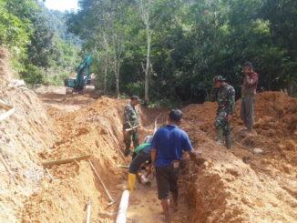 Pemindahan pipa air yang mengganggu kelancaran proyek pisik kegiatan TMMD pembangunan jalan.