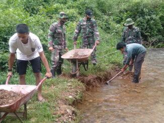 Anggota TMMD komsos sambil membantu usaha warga mengambil krikil di sungai.