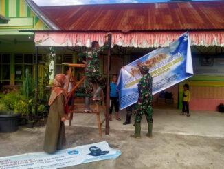 Anggota satgas TMMD membantu pihak sekolah melakukan berbagai kegiatan,ternasuk memasang spanduk.