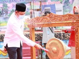 Bupati Epyardi Asda memukul gong tanda resminya penggunaan aplikasi layanan mandiri smart.