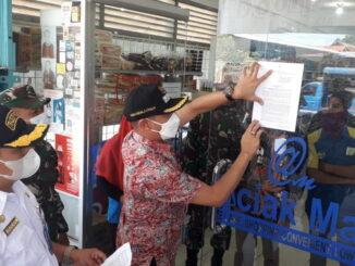 Camat Heriza Syafani saat melakukan penempelan SE Walikota Padang terkait PPKM.