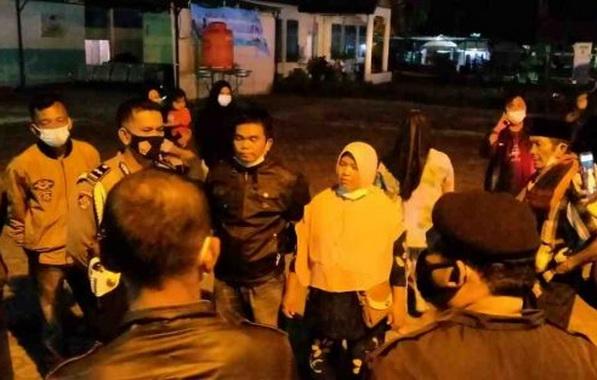 Petugas polisi saat berdialog dengan keluarga jenazah pasien Covid-19.