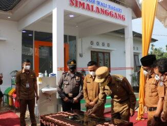 Bupati Linapuluh Kota tengah menandatangani prasasti peresmian kantor Walinagari Simalanggang..