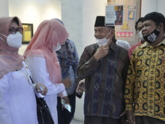 Amir Syarif, sang maestro pelukis kaligrafi Islam menjelaskan karya-karyanya kepada staf ahli gubernur Enifita Djinis, SH.