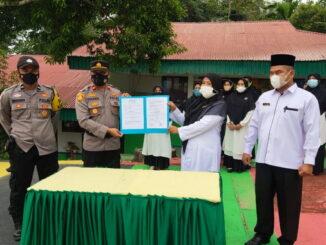 Kapolsek bersama Kepala MAN I Palangki memperlihatkan naskah perjanjian kerjasama tentang keamanan dan ketertiban sekolah,